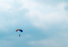 Distant View Of Man Parachuting Down Against Cloudy Sky