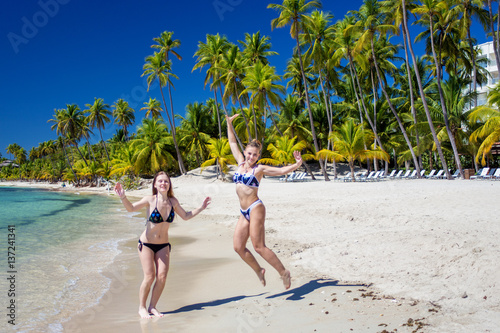 f08820b686fec two girls in bikini jumping on tropical beach on a background of blue sky  and palm