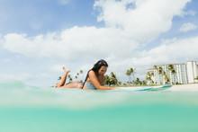 Surface Level View Of Woman Lying On Surfboard, Oahu, Hawaii, USA