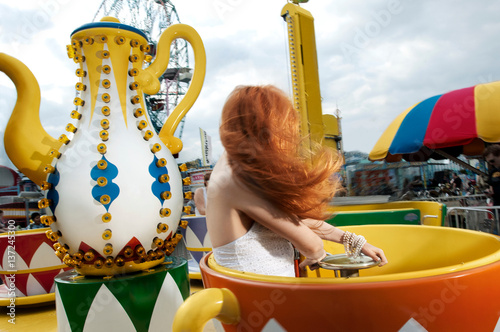 Poster Amusementspark Young woman with long red hair on teacup amusement park ride, Coney Island, New York, USA