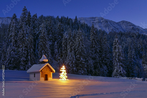 Leinwand Poster Illuminated Christmas tree in front of a chapel in winter, Bavaria, Upper Bavari