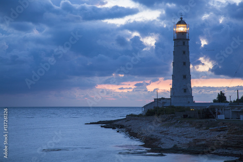 blue twilights around old lighthouse on the sea coast