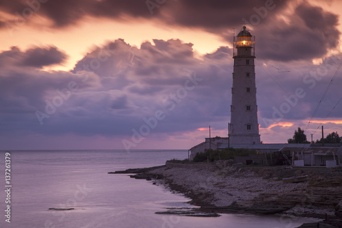 Montage in der Fensternische Leuchtturm colored sunset and lighting lighthouse on the sea coast