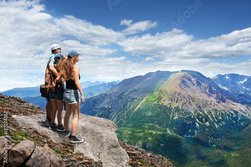 Fotografie, Obraz  Father with arms around his family looking at beautiful summer mountains landscape, on hiking trip, on  top of  mountain rock