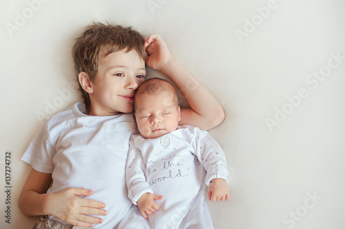 Photo older brother hugging his newborn sister