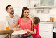 Happy parents and daughter on kitchen
