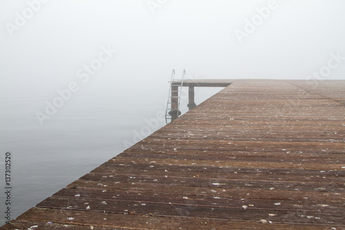 A wooden pier and stairs to sea in a foggy day. Most of the photo is covered with the wooden pear.