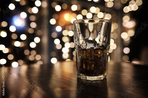 Foto glass of alcohol with ice on blured background with circle bokeh
