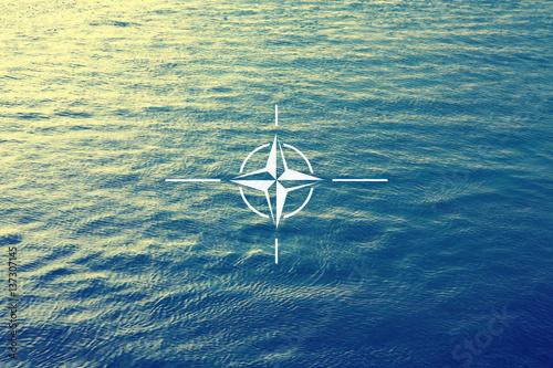 Photo  Beautiful dark blue sea wave pattern with Nato flag organization symbol background
