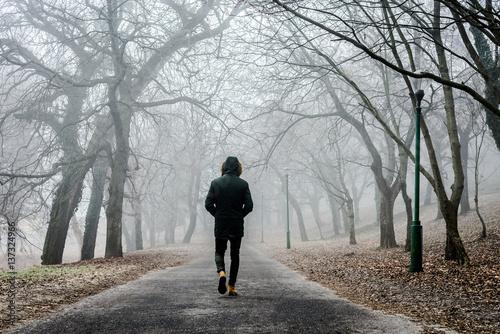 Foto  man walking through a fog forest