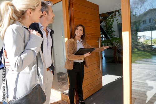 Fotografía  Real estate agent inviting couple to enter house for visit
