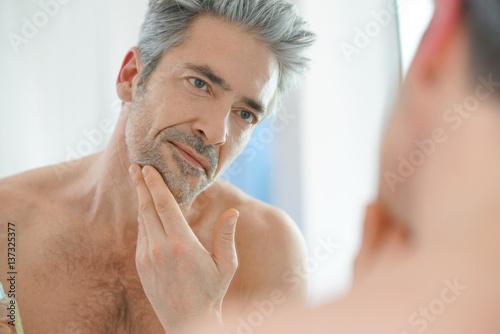 Fotografie, Obraz  Portrait of mature man in front of mirror applying facial cream