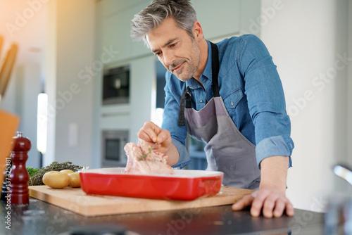 Foto op Plexiglas Koken Mature man in kitchen cooking dish for dinner