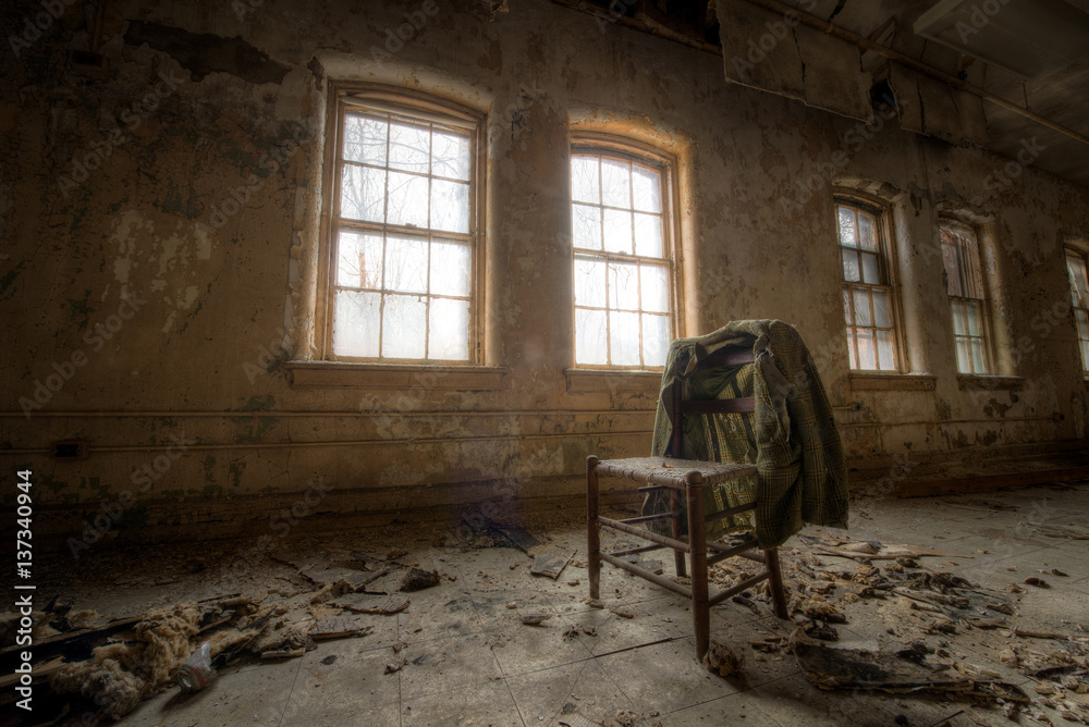 Fototapeta Old suit coat hanging on a chair in an abandoned room