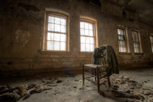 Old Suit Coat Hanging On A Chair In An Abandoned Room