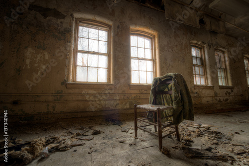 Old suit coat hanging on a chair in an abandoned room Wallpaper Mural
