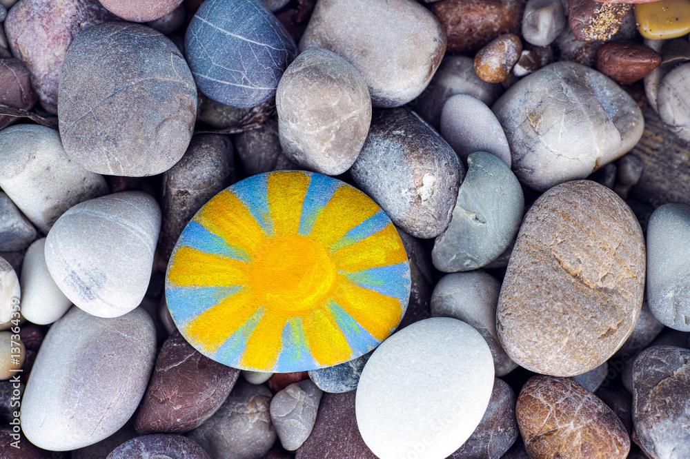 Fototapeta Sun painted on pebble with stones background