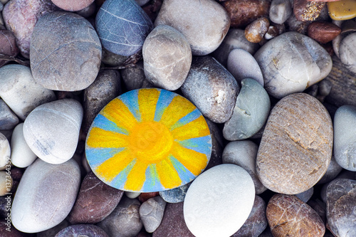 Fotografía  Sun painted on pebble with stones background