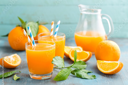 Photo  Orange juice in glass and fresh fruits with leaves on wooden background, vitamin