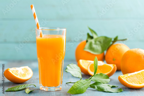 Foto auf Leinwand Saft Orange juice in glass and fresh fruits with leaves on wooden background, vitamin drink or cocktail