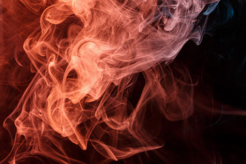 Abstract smoke Weipa. Personal vaporizers fragrant steam. Concept of alternative non-nicotine smoking. Turquoise orange smoke on a black background. E-cigarette. Evaporator. Taking Close-up. Vaping.