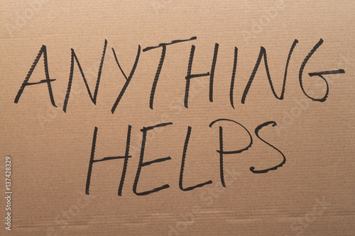 Thw words Anything Helps written on a carboard sign Canvas Print