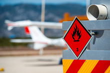 Rear View Of Service And Refuelling Truck On An Airport With An Aircraft In The Blurry Background. Chemical Hazard, Flammable Liquids.