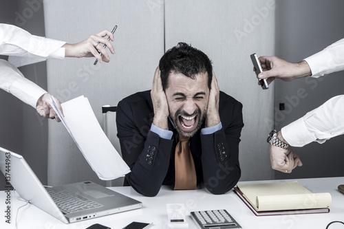 Obraz manager al centro è disperato mentre tante mani gli danno compiti. Tiene le mani nelle orecchi e urla. - fototapety do salonu