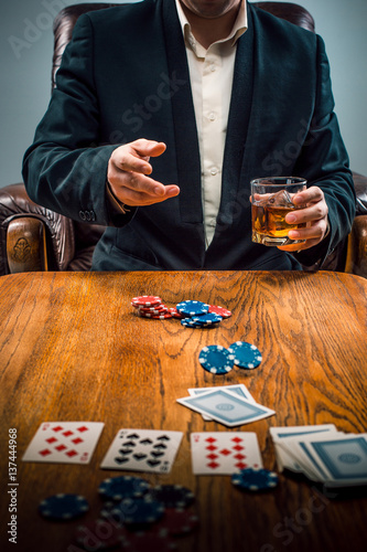 The man, chips for gamblings, drink and playing cards плакат