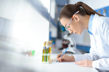 side view of scientist writing down test results while working in laboratory