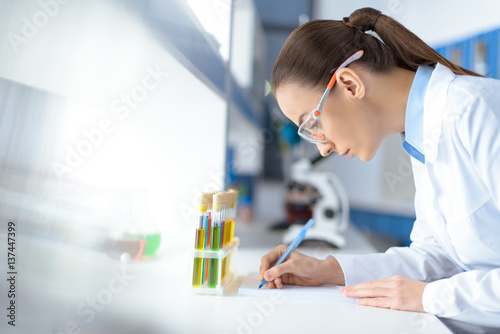 Valokuva  side view of scientist writing down test results while working in laboratory