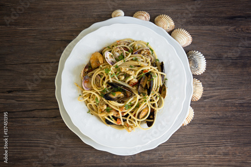 Poster Coquillage Spaghetti with seafood in white ceramic plate on wooden background