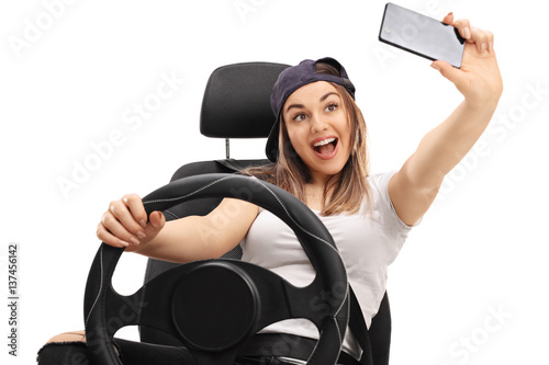 Fotografia, Obraz  Cheerful girl sitting in car seat and taking selfie