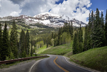 Snowcapped Rocky Mountains In The Background With A Winding Mountain Road Stretching Into The Distance; Colorado, United States Of America