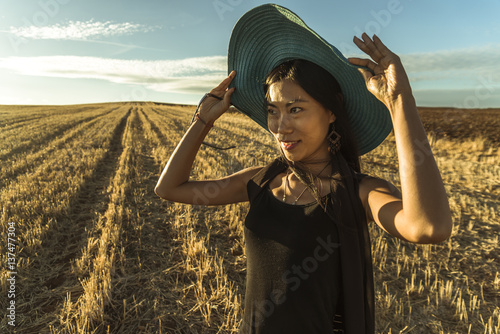 Chinese young woman walking in a wheat field; Madrid Spain
