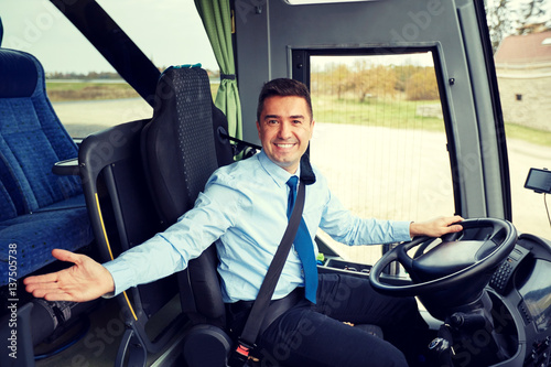 happy driver inviting on board of intercity bus