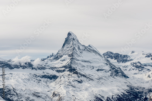 Fotomural Scenic moody view on snowy Matterhorn peak with sky and clouds in background, Switzerland