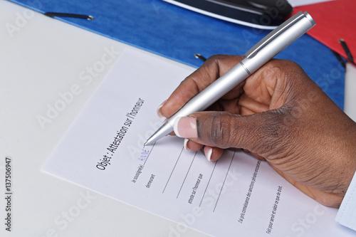 Photo main femme noire signant une attestation sur l'honneur