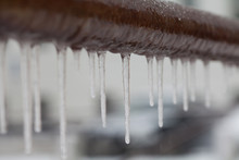 Icicles Hanging From A Brown P...