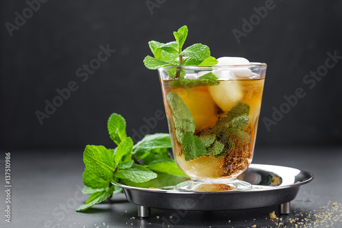 Valokuvatapetti Mint Julep cocktail with bourbon, ice and mint in glass on black background