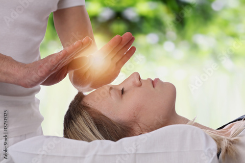 Woman having reiki healing treatment , alternative medicine concept.