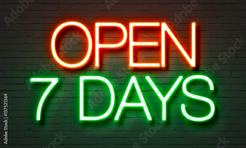 Photo  Open 7 days neon sign on brick wall background.