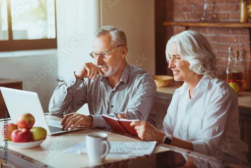 Fototapeta Positive aged couple sitting in the kitchen obraz