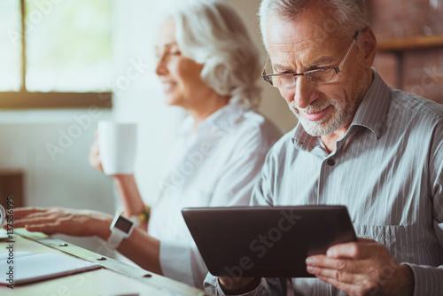 Fotografía  Pleasant aged man using tablet
