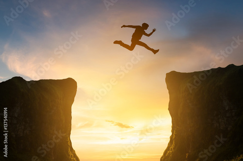 man jumping over the cliff, silhouette Canvas Print