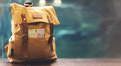 Fototapeta Hipster yellow backpack and map closeup. View from front tourist traveler bag on background blue sea aquarium. Person hiker visiting oceanarium museum in Barcelona on backdrop, blank blurred mockup obraz