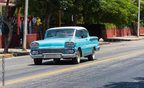 Türaufkleber Autos aus Kuba Blauer Oldtimer mit weißem Dach fährt auf der Straße durch Varadero Kuba - Serie Kuba Reportage
