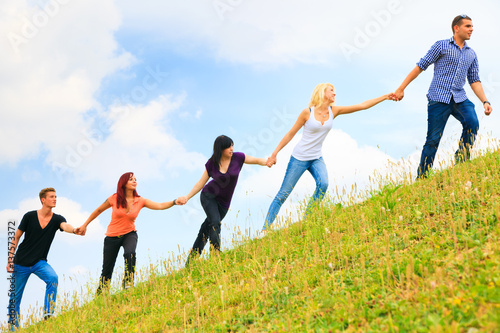 Fotomural  Young People Helping Each Other Climb A Hill
