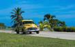 Amerikanischer gelber Oldtimer fährt auf der Küstenstraße nach Santa Clara Kuba - Serie Kuba Reportage