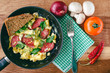 Fresh cooked scrambled eggs in pan with sausage and herbs. Bread, fork, vegetables, napkin on wooden board, top view.